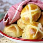 Golden, baked hot cross buns on a tray with a red tea towel over them.