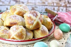 Hot cross buns on a tray with colored eggs on the table nearby.