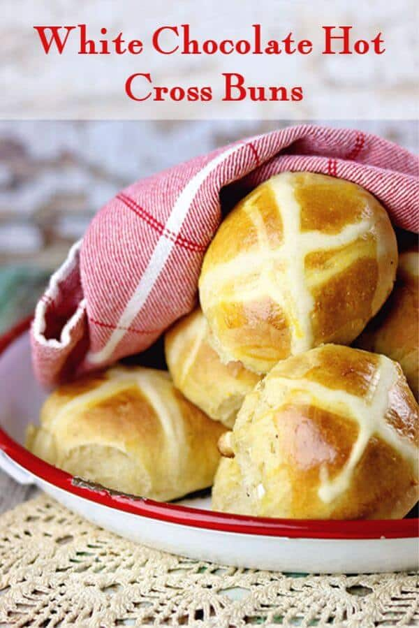Baked hot cross buns in a white and red tray ready to eat.