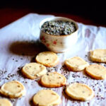 Baked cookies on a piece of parchment with dried lavender flowers.
