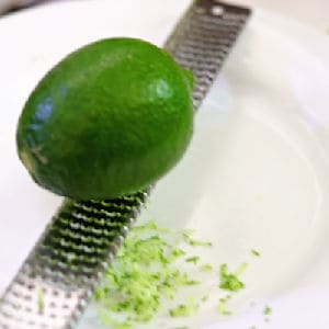 A lime on a microplane being grated into a bowl.
