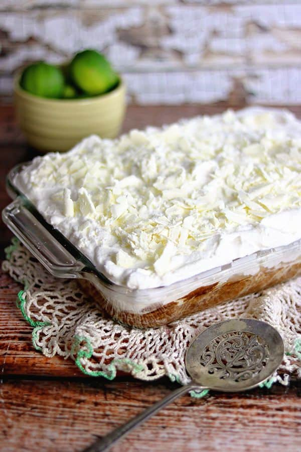 A cake covered in whipped cream and white chocolate on a wooden table.