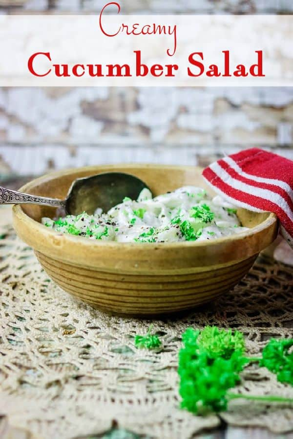 Bowl of cucumber salad on a lace table cloth. Text overlay: Creamy Cucumber Salad