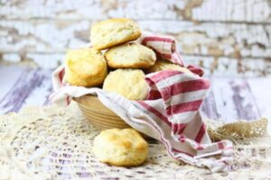 Buttermilk biscuits in a bowl with a red striped towel.