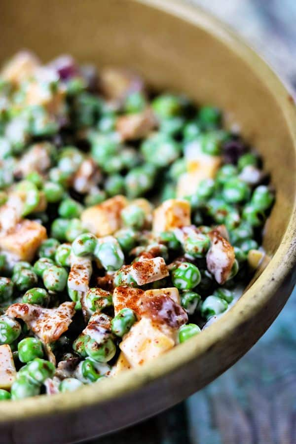 Close up image of green peas, bacon, and diced cheddar in this pea salad recipe.