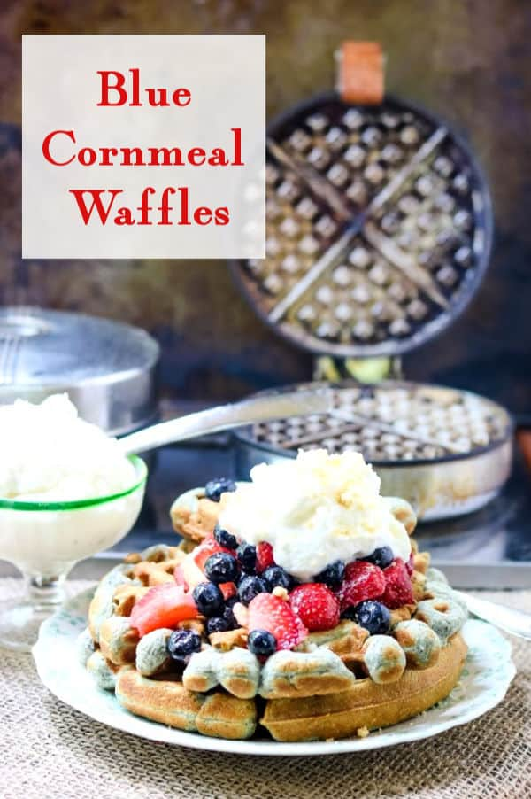 close up of a stack of waffles with strawberries and blueberries on top - title overlay
