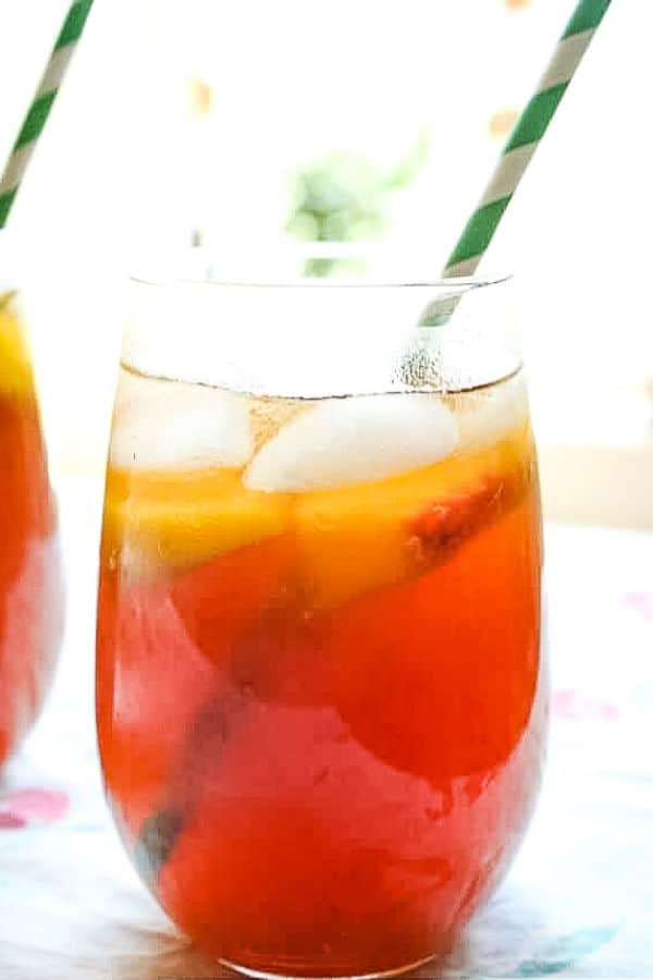 Bourbon peach tea in two glasses with green straws.