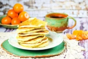 stack of buttermilk pancakes with oranges in the background.