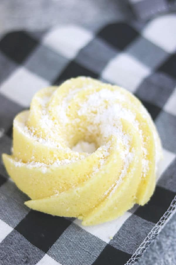 close up of a lemon chardonnay pound cake on a black and white checked napkin