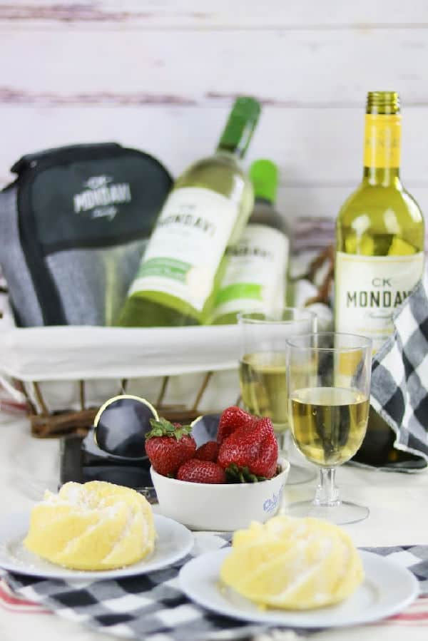 A picnic scene with wine bottles, berries, and pound ccake
