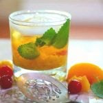 A peach bourbon mule in an on the rocks glass garnished with mint