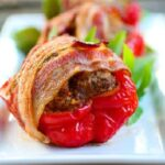closeup of meatloaf stuffed red bell peppers wrapped in crispy bacon - recipe card image.