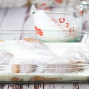 Raw chicken breast marinating in buttermilk