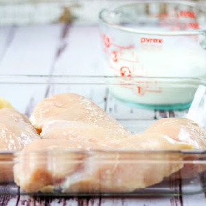 Raw chicken breast in a dish.