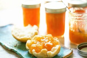 Sweet apricot jam on biscuit with jars of jam.