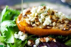Grilled pear with blue cheese. Honey being drizzled on top.