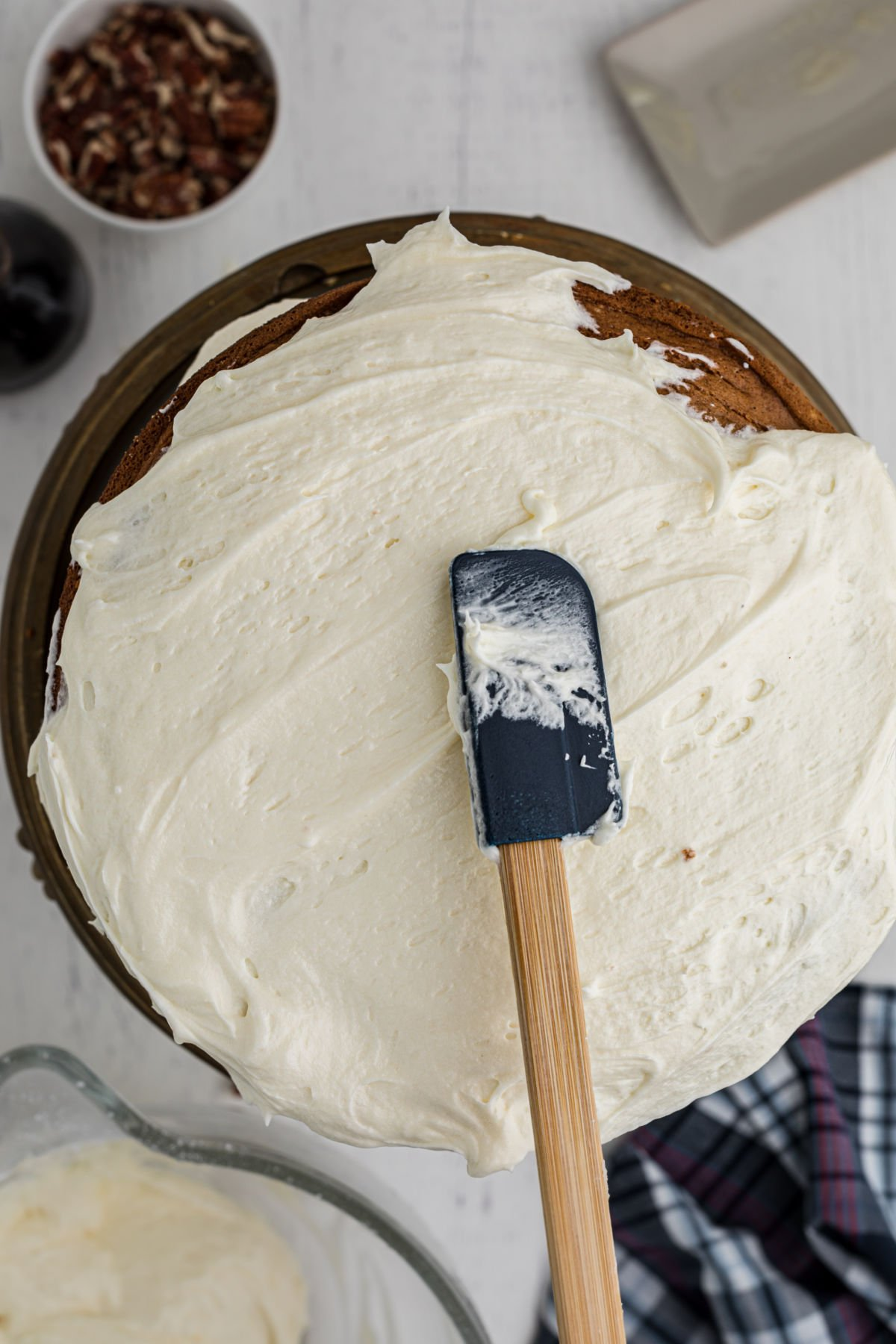 Putting frosting on the cake with a rubber spatula.