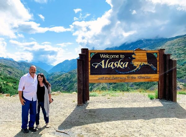 A Welcome to Alaska sign with Marye Audet-White and Marc White