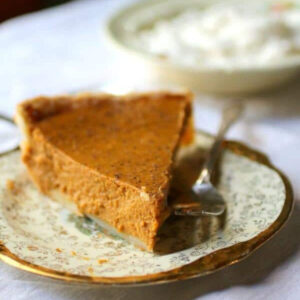 Slice of pumpkin pie on a gold rimmed plate.