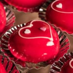 Close up of chocolate candy covered in a red glaze with hearts on it.