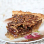 Close up of a slice of old fashioned southern pecan pie with the filling running out of the sides.