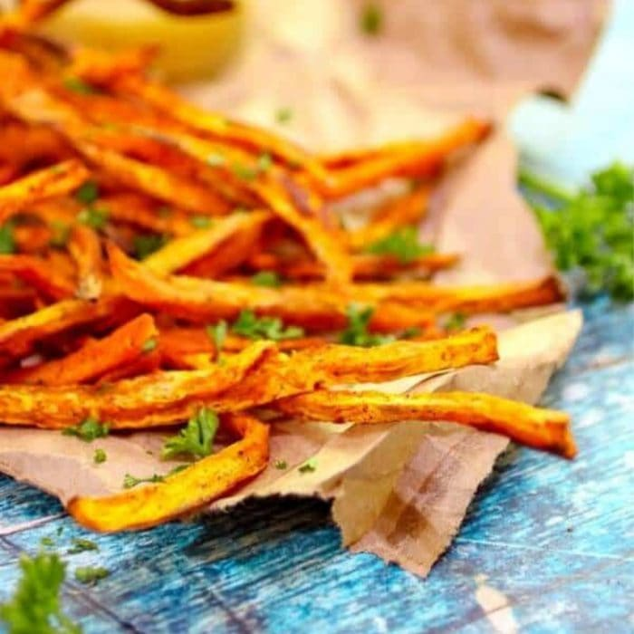 close up of sweet potato fries on a blue table.