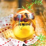 Apple cider sangria with cranberries and cinnamon sticks in a wine glass.
