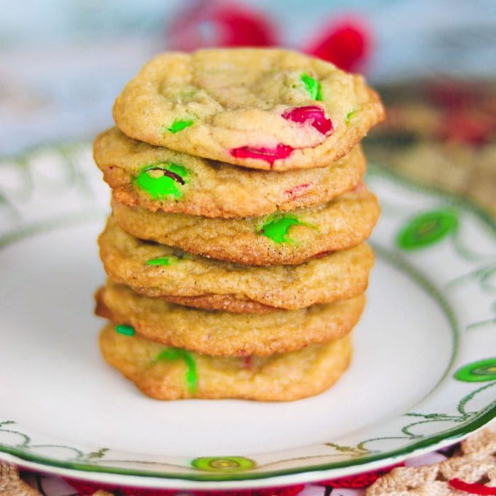 stack of m&ms cookies with red and green candies on a white plate with green trim.