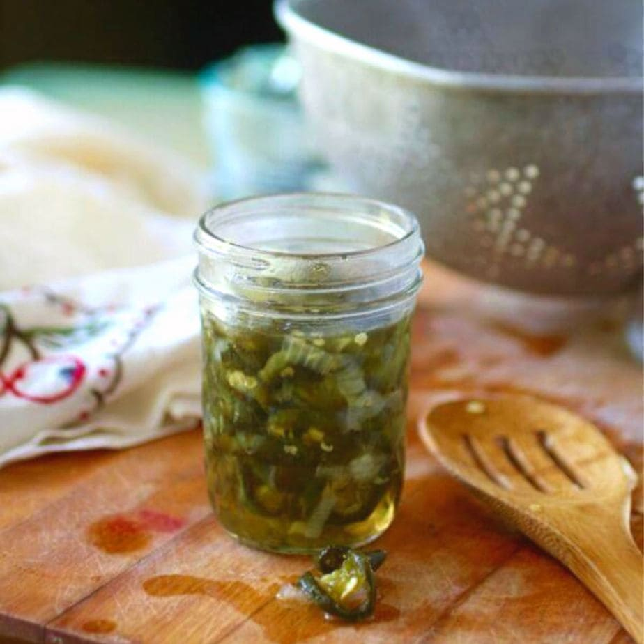 A glass jar of candied jalapenos on a wooden surface.