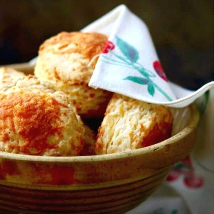 Big, fluffy, flaky cheese biscuits in a bowl.