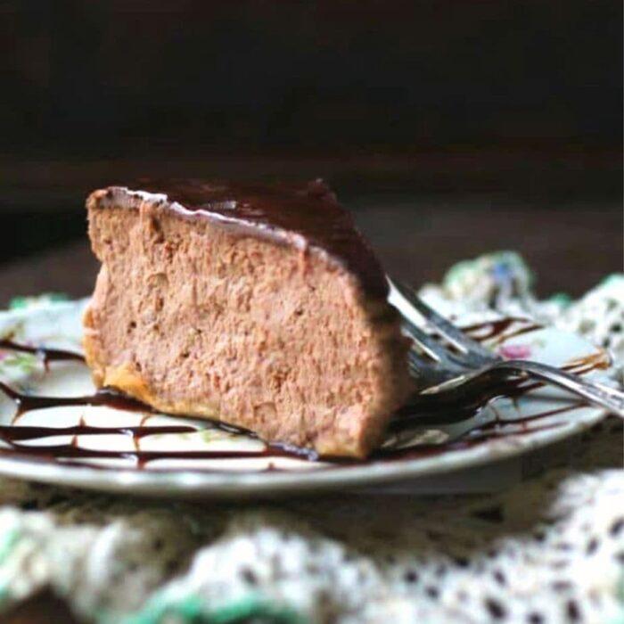 slice of chocolate Irish cream cheesecake with a shiny chocolate glaze