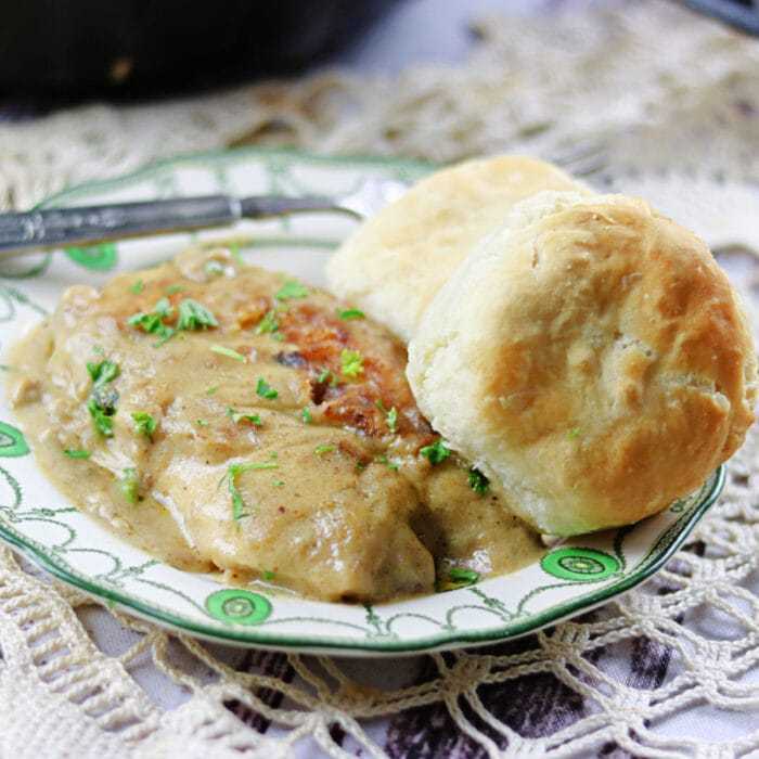 Smothered chicken and gravy on a plate with biscuits.