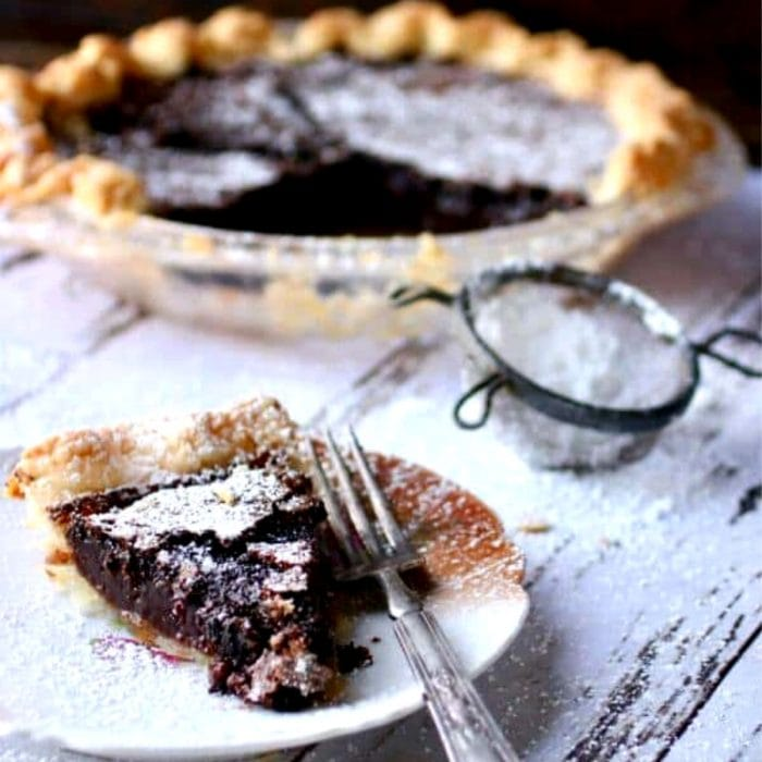 Slice of chocolate chess pie on a vintage plate.