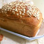 Uncut loaf of honey oatmeal bread showing the finished product