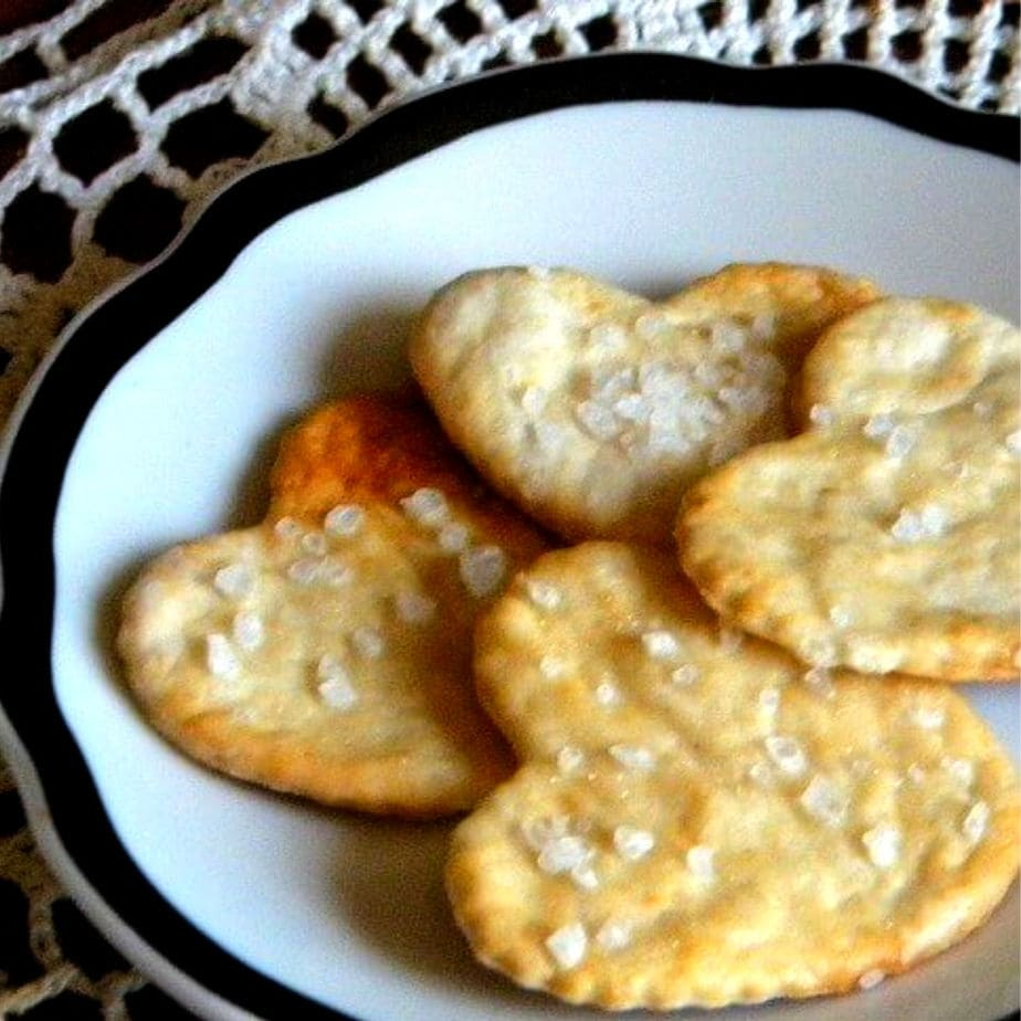Homemade saltine crackers cut in heart shapes on a black and white plate.