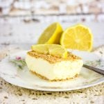A square of lemon cheesecake on a flowered plate with a lemon slice on top.