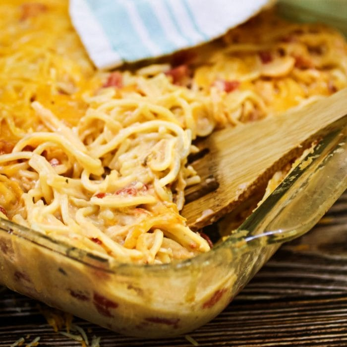 Chicken spaghetti in a casserole dish with a wooden spoon in it.