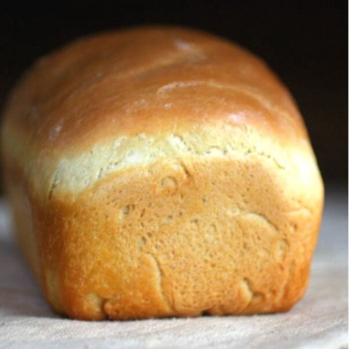 Baked loaf of white bread, uncut.