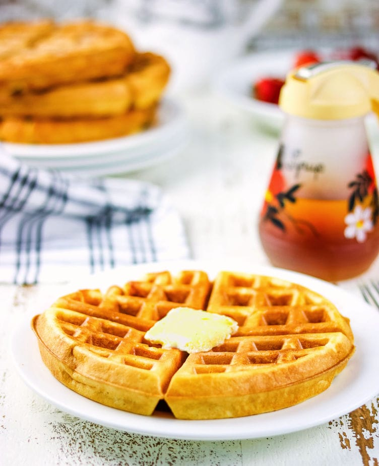 A finished waffle on a pate with a stack of waffles in the background.