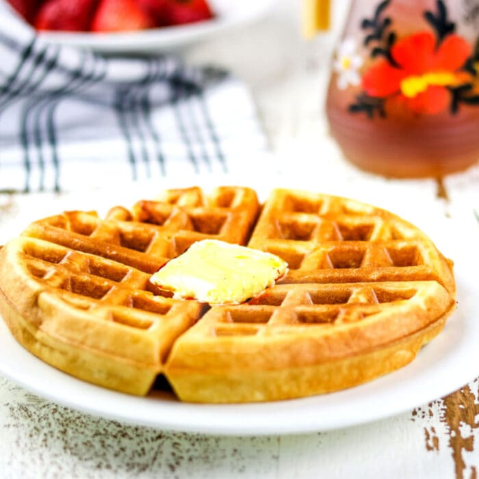 Closeup of a finished waffle with butter on top.