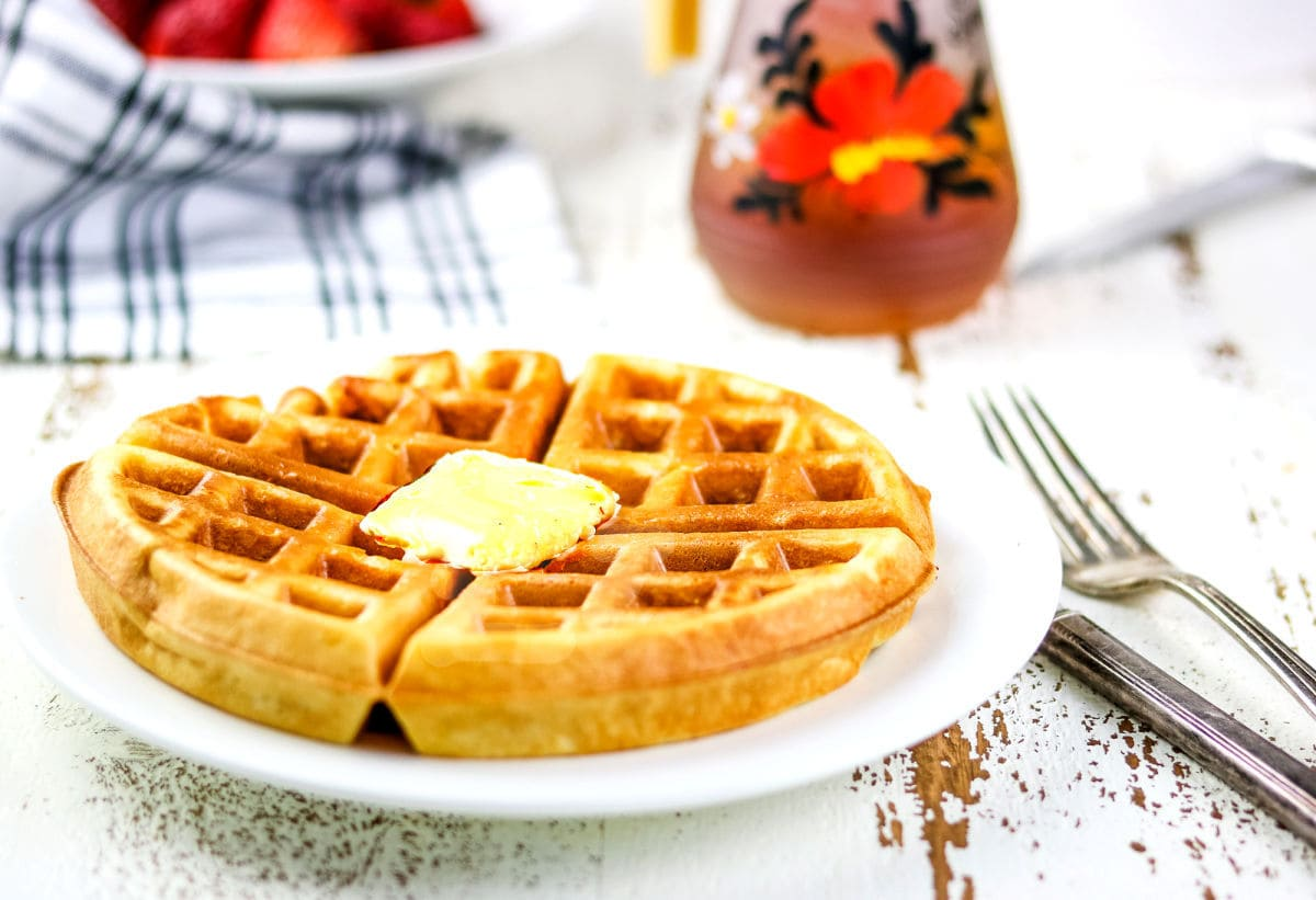 A plate of waffles with strawberries and syrup.
