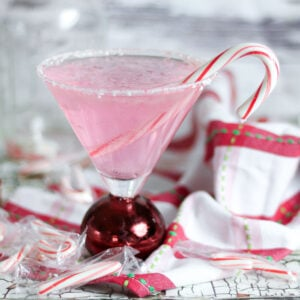 Pink peppermint martini with a candy cane garnish.