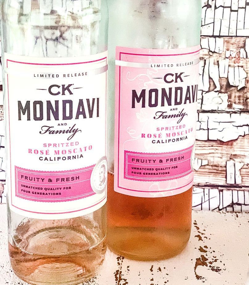Two bottles of CK Mondavi and Family Spritzed Rose Moscato showing the label turns pink when chilled.