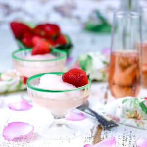 Pink rose moscato sorbet in small sherbet glasses garnished with strawberries.
