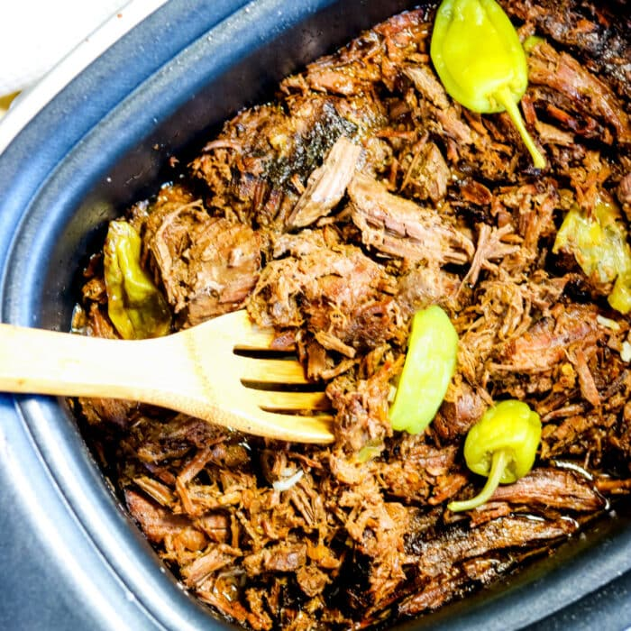 Close up of shredded pot roast meat in a slow cooker.