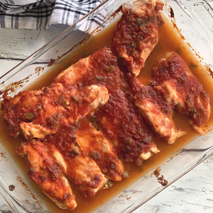Chicken breasts in a glass baking pan.