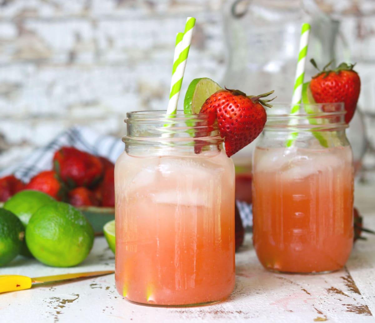 Two Mason jars of strawberry vodka lemonade ready to drink.