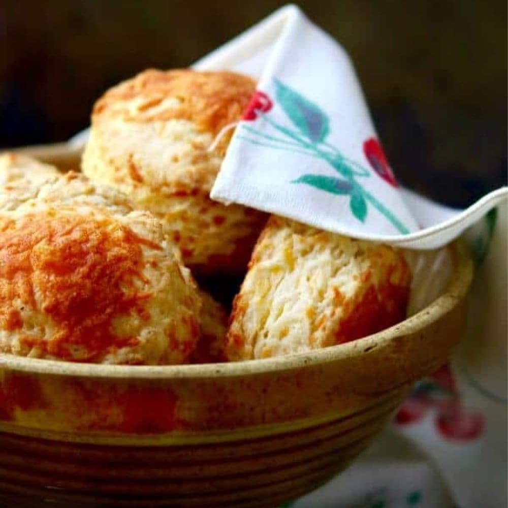 Big, flakey biscuits in a yellow ware bowl