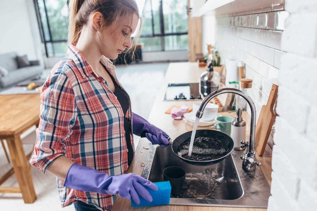 A woman cleaning up the kitchen.