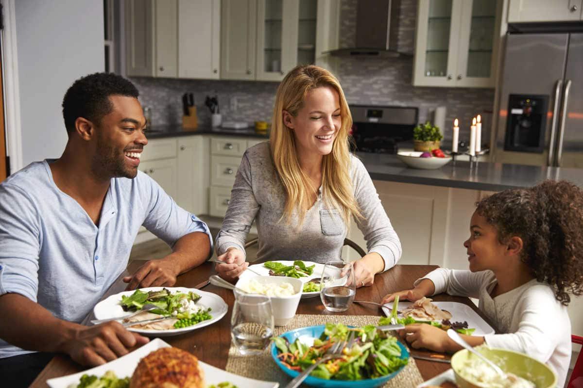 A biracial enjoying a family dinner.